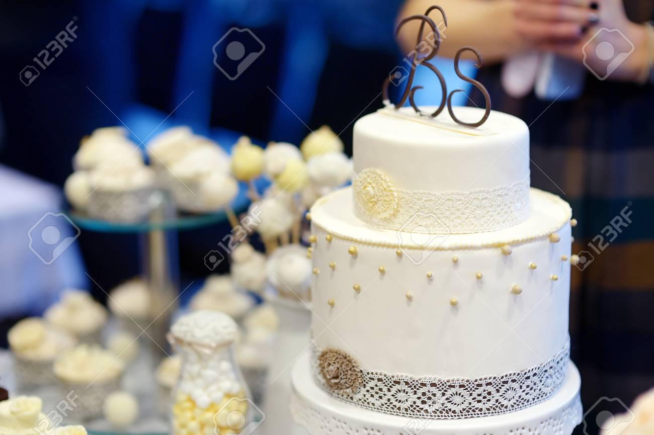 White Wedding Cake Decorated With White Lace And Pearls Stock Photo ...