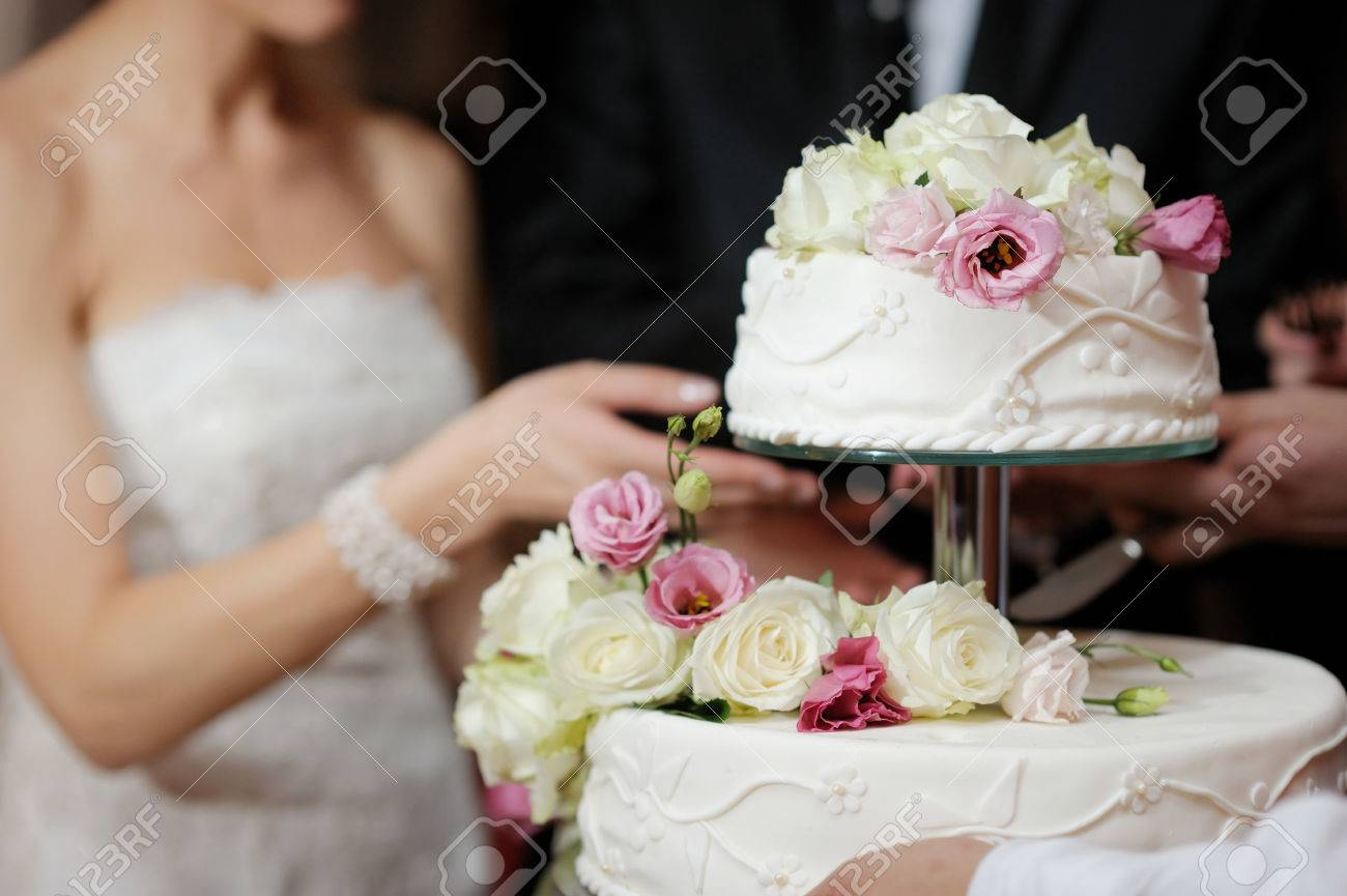 A bride and a groom is cutting their wedding cake Stock Photo - 40791950