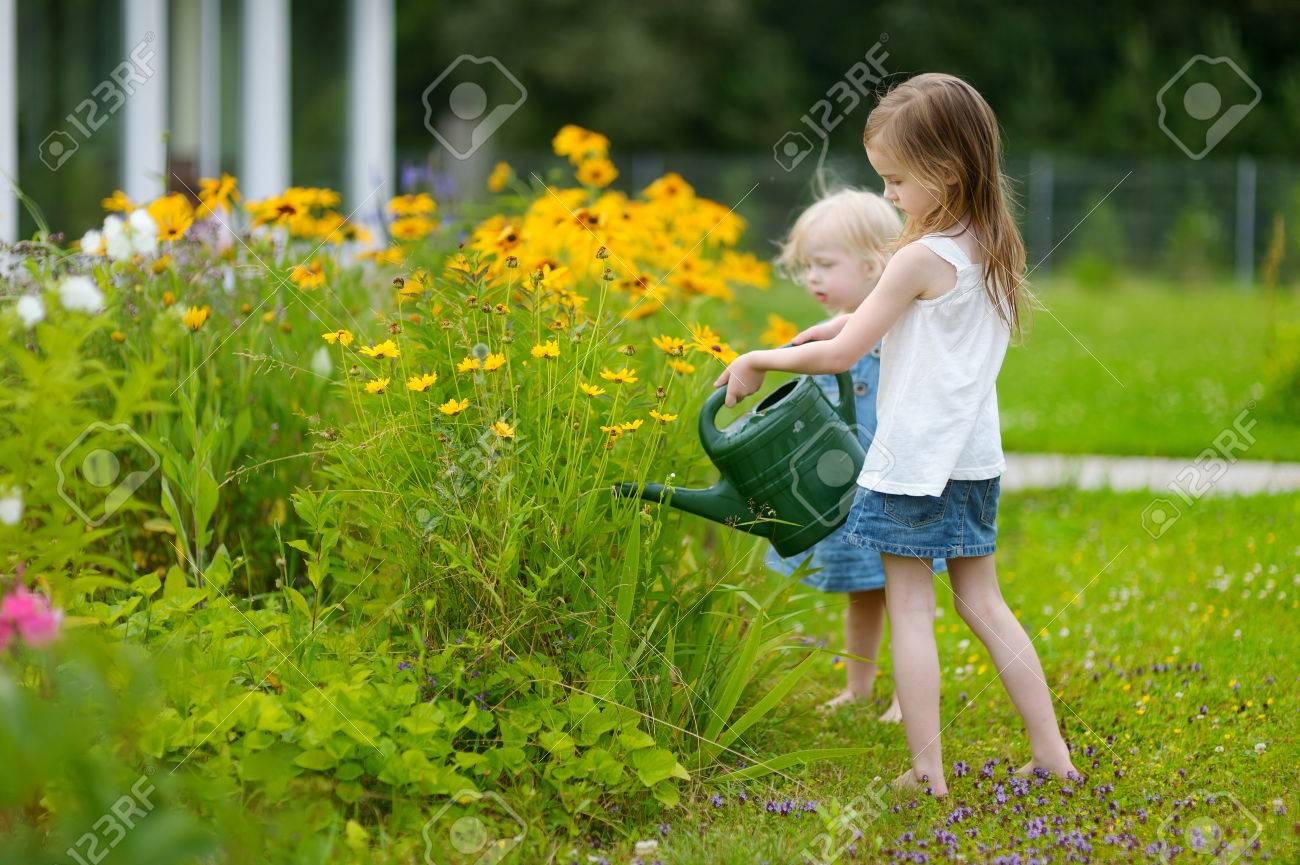 Adorable Little Preschooler Girl Watering Pretty Yellow Flowers