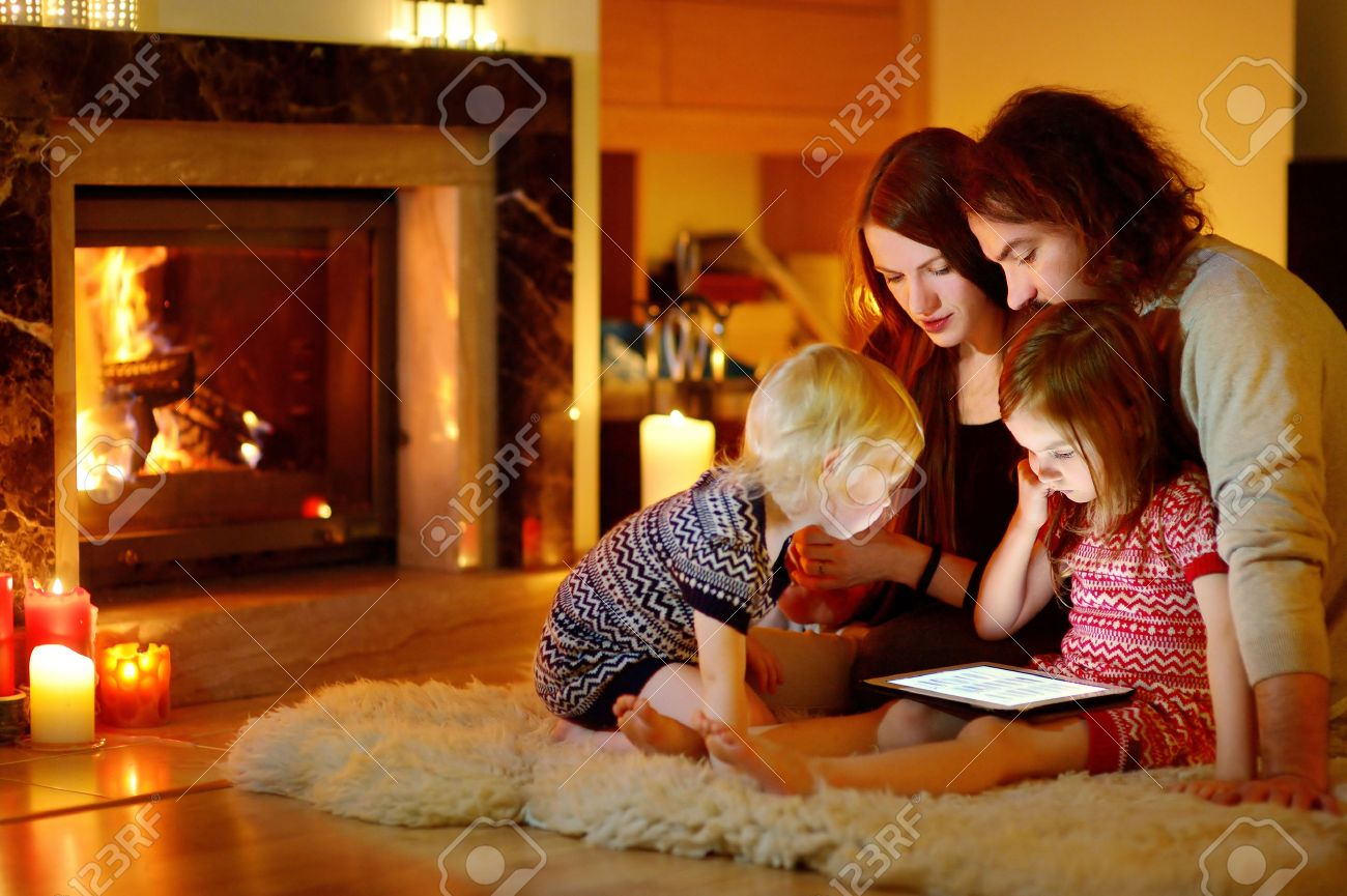 happy young family using a tablet pc at home by a fireplace in