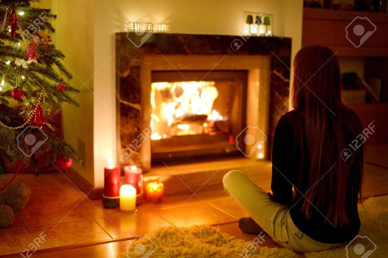 Junge Frau Durch Einen Kamin In Einem Gemütlichen Dunklen Wohnzimmer ...