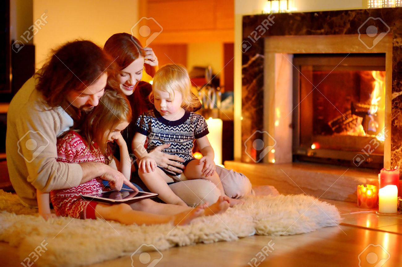 Happy Young Family Using A Tablet Pc At Home By A Fireplace In ...