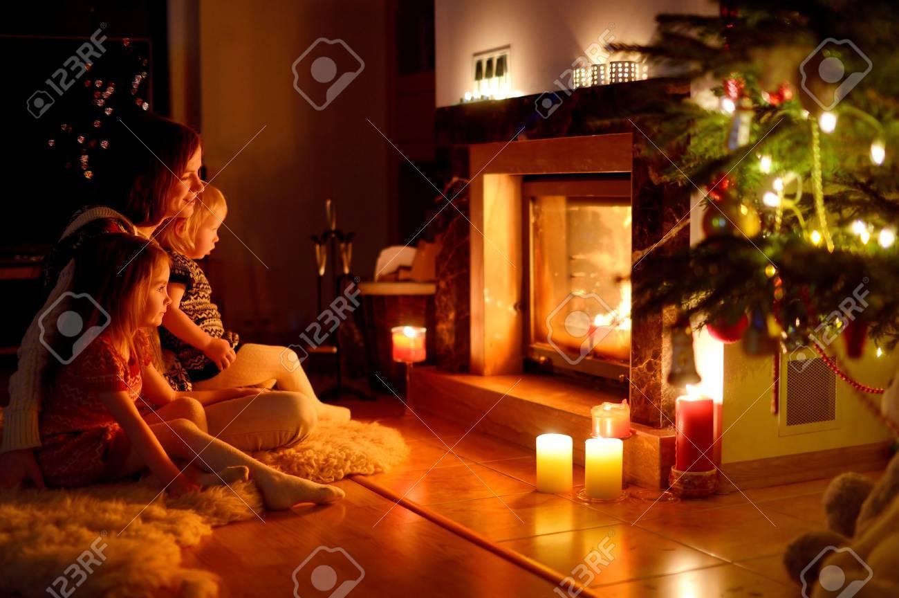 Junge Mutter Und Ihre Zwei Kleinen Töchter Sitzen Durch Einen Kamin In  Einem Gemütlichen Dunklen Wohnzimmer