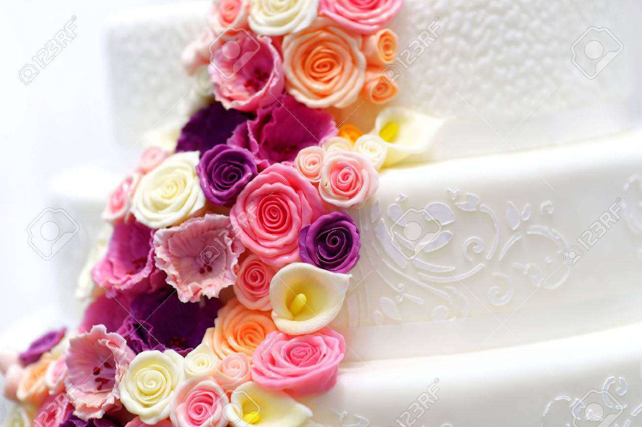 Detail Of A White Wedding Cake Decorated With Pink Sugar Flowers