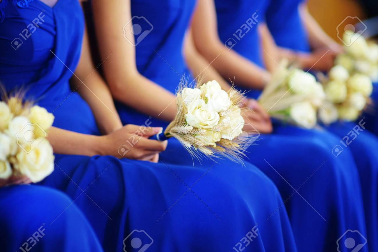rangée de demoiselles d'honneur vêtues de robes bleues tenant des