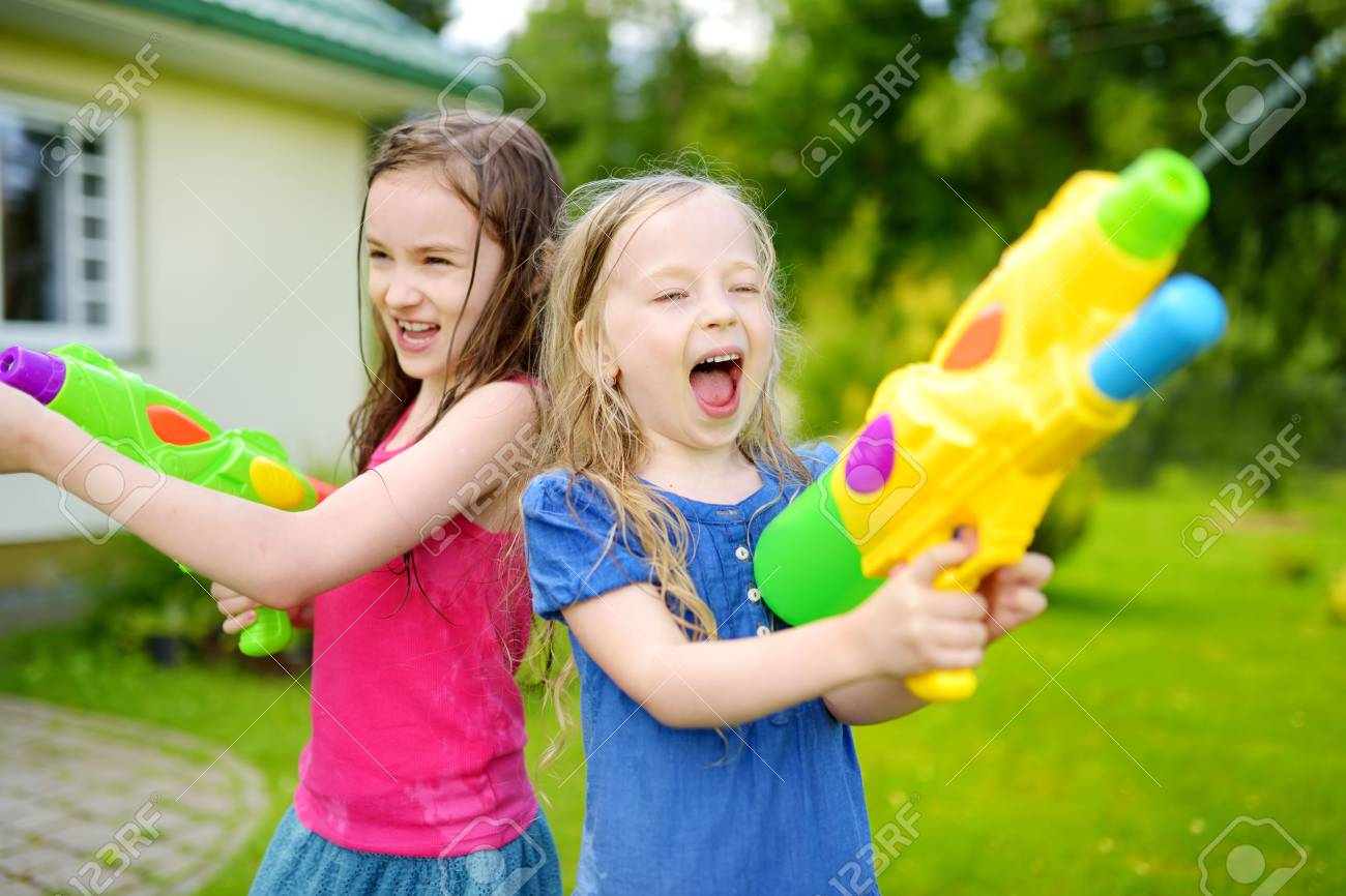 Adorable little girls playing with water guns on hot summer day