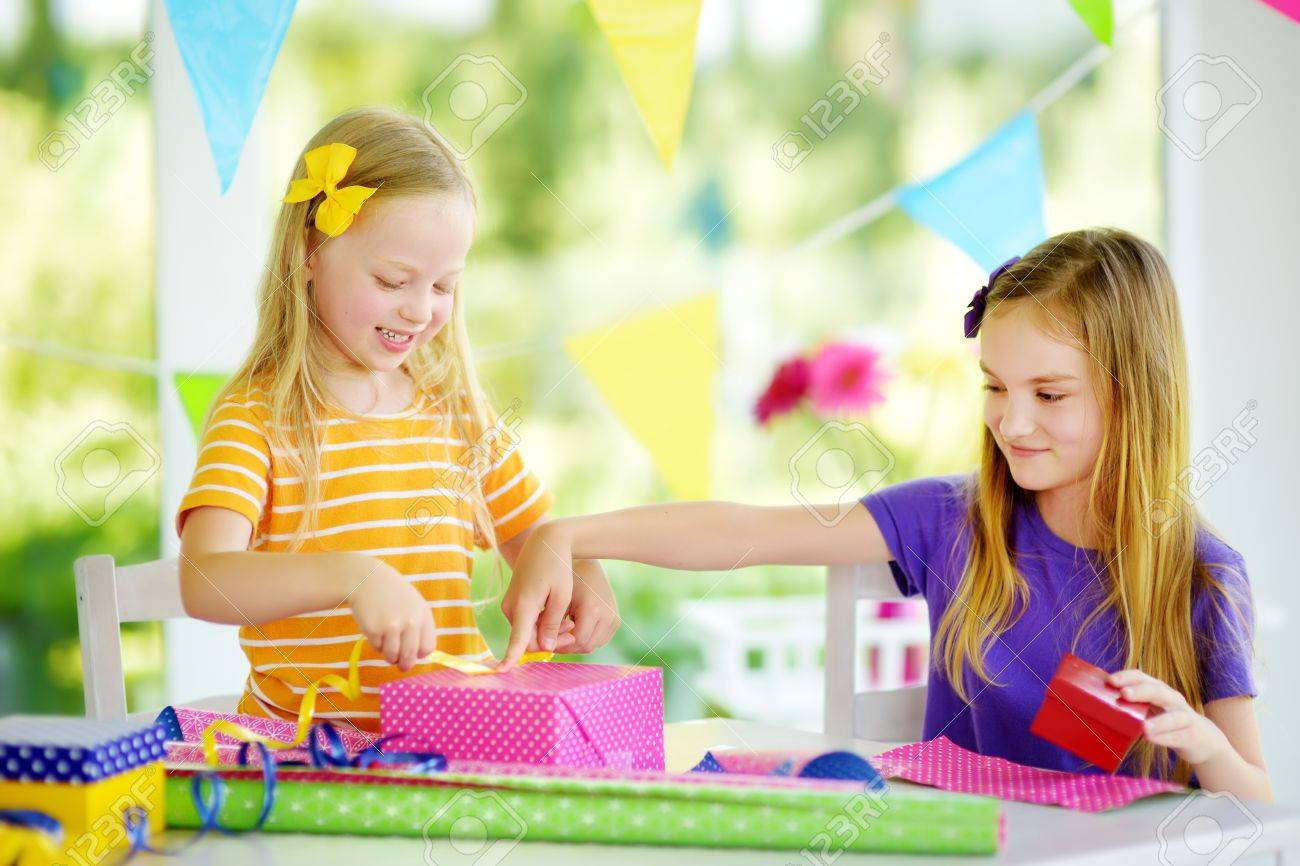 Two Cute Sisters Wrapping Gifts In Colorful Paper Adorable