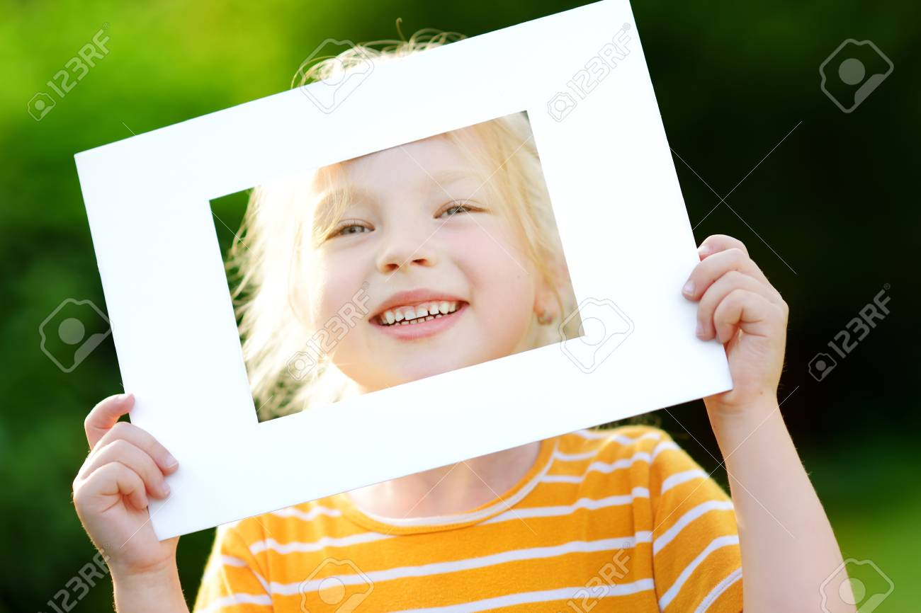 Cute Cheerful Little Girl Holding White Picture Frame In Front