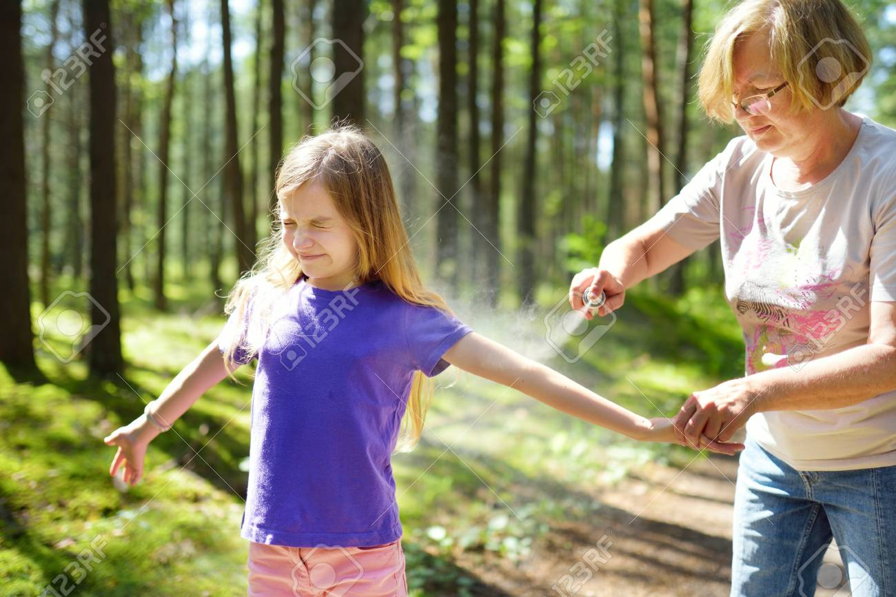 Middle age woman applying insect repellent to her granddaughter before forest hike beautiful summer day. Protecting children from biting insects at summer. Active leisure with kids. - 96051069