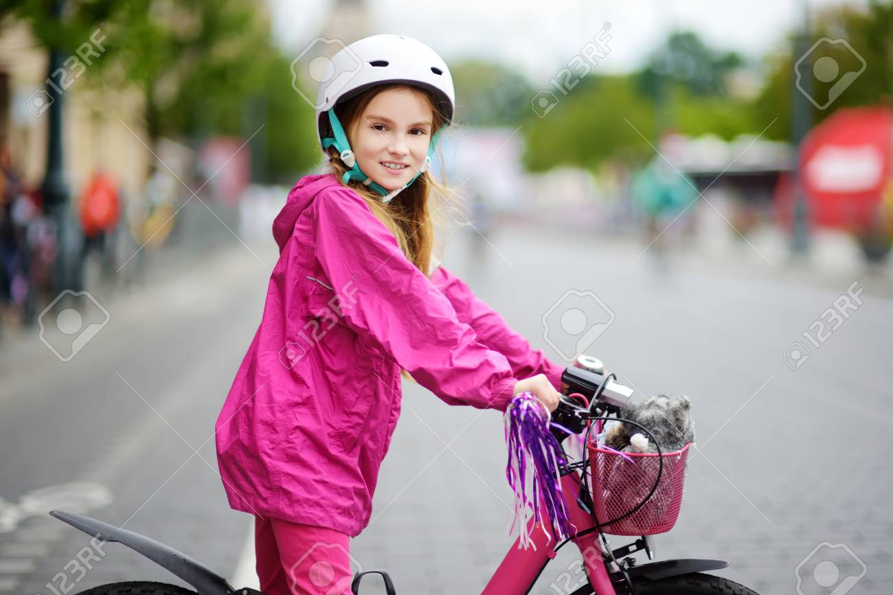 Cute Little Girl Riding A Bike In A City Wearing Helmet On Summer Stock Photo Picture And Royalty Free Image Image 96050736