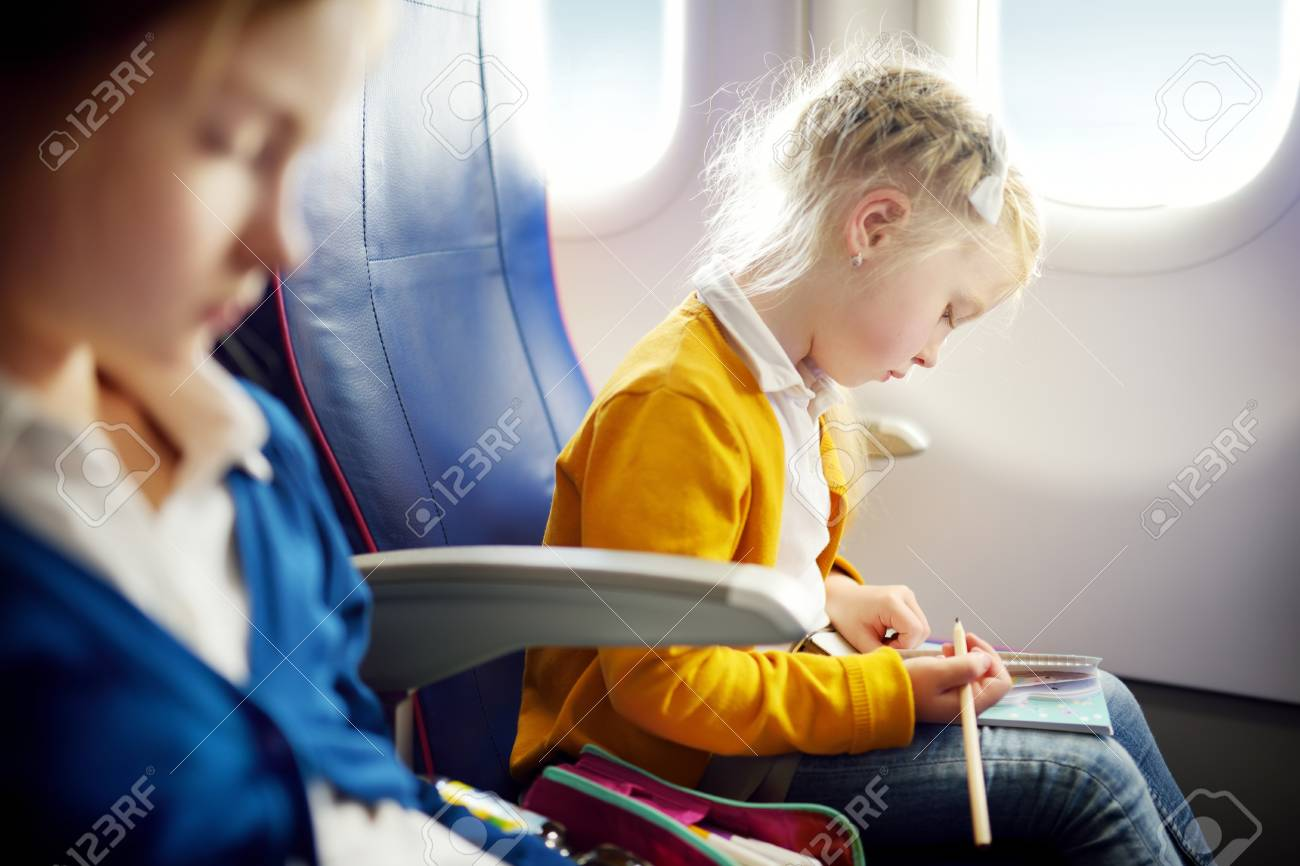 Adorable little girls traveling by an airplane child sitting by aircraft window and drawing a