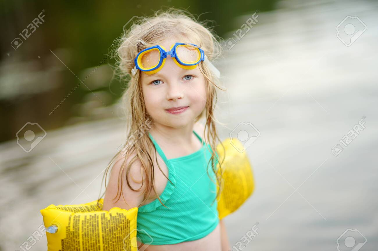 Cute young girl wearing swimsuit playing by a river on hot summer..