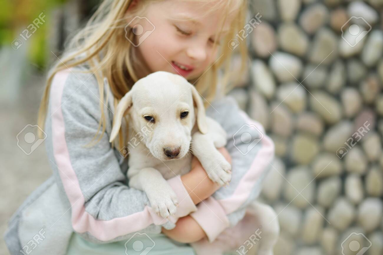 Cute Little Girl Holding Small White Puppy Outdoors Kid Playing Stock Photo Picture And Royalty Free Image Image 119882059