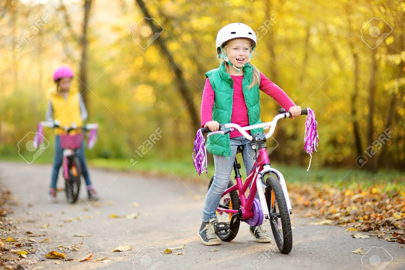 Cute little sisters riding bikes in a city park on sunny autumn day. Active family leisure with kids. Children wearing safety helmet while riding a bicycle. - 127127419