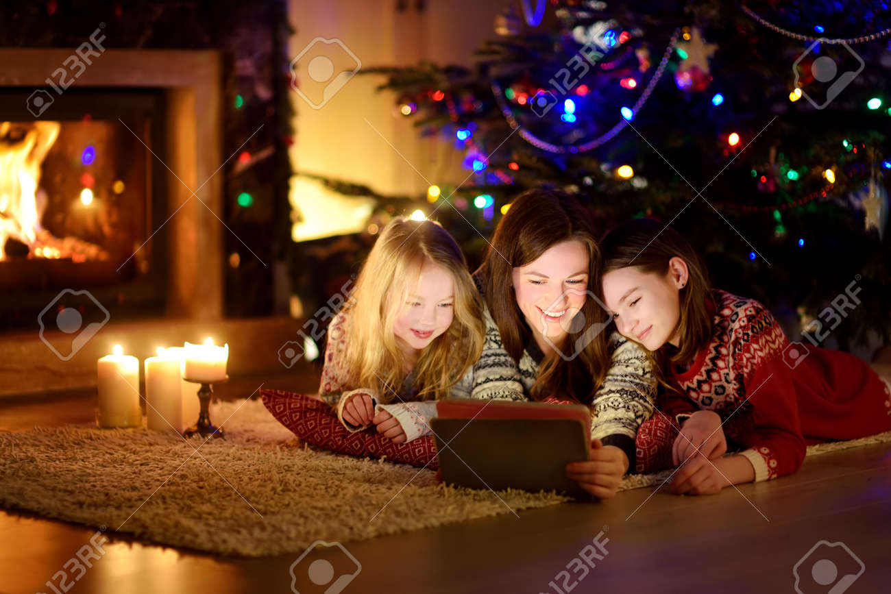 Mother and her two cute young daughters using a tablet pc at home by a fireplace in warm and cozy living room on Christmas eve. Winter evening at home with family and kids. - 133502257