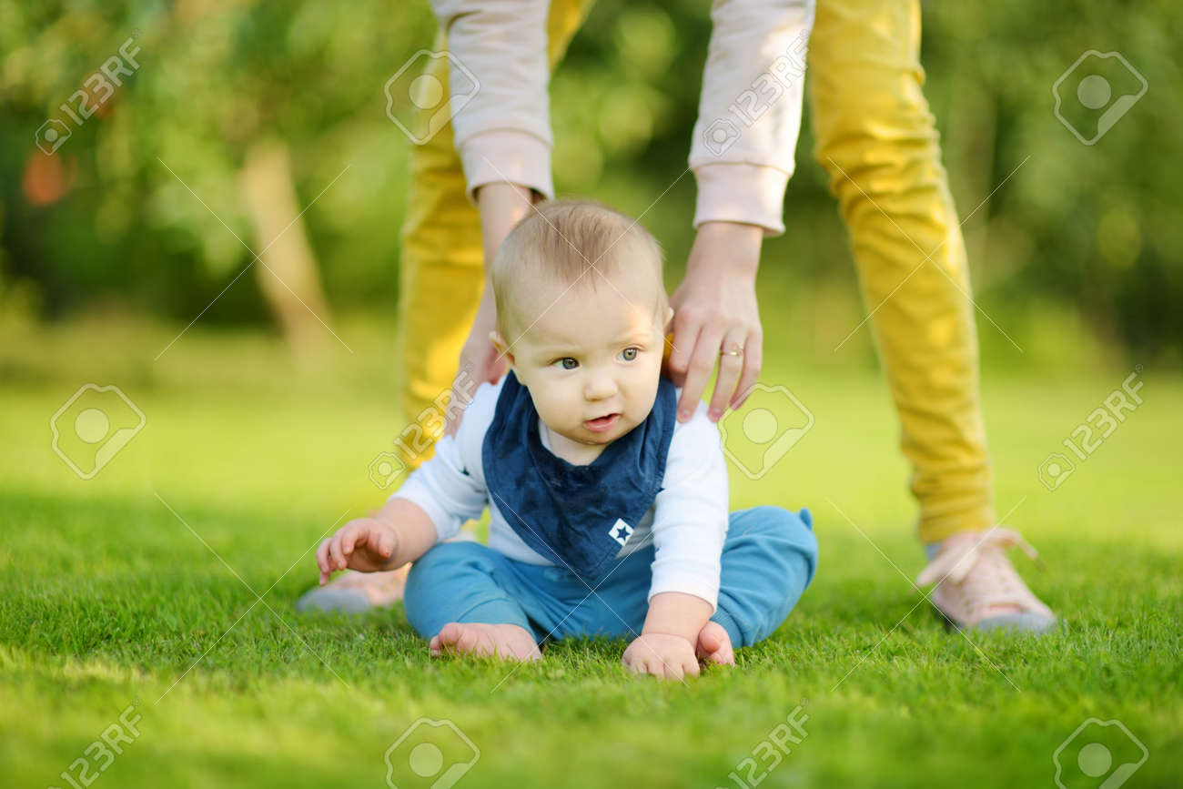 Cute five months old baby boy learning how to sit up without support. Baby during floortime. Adorable little child trying to sit up on his own. - 166230268