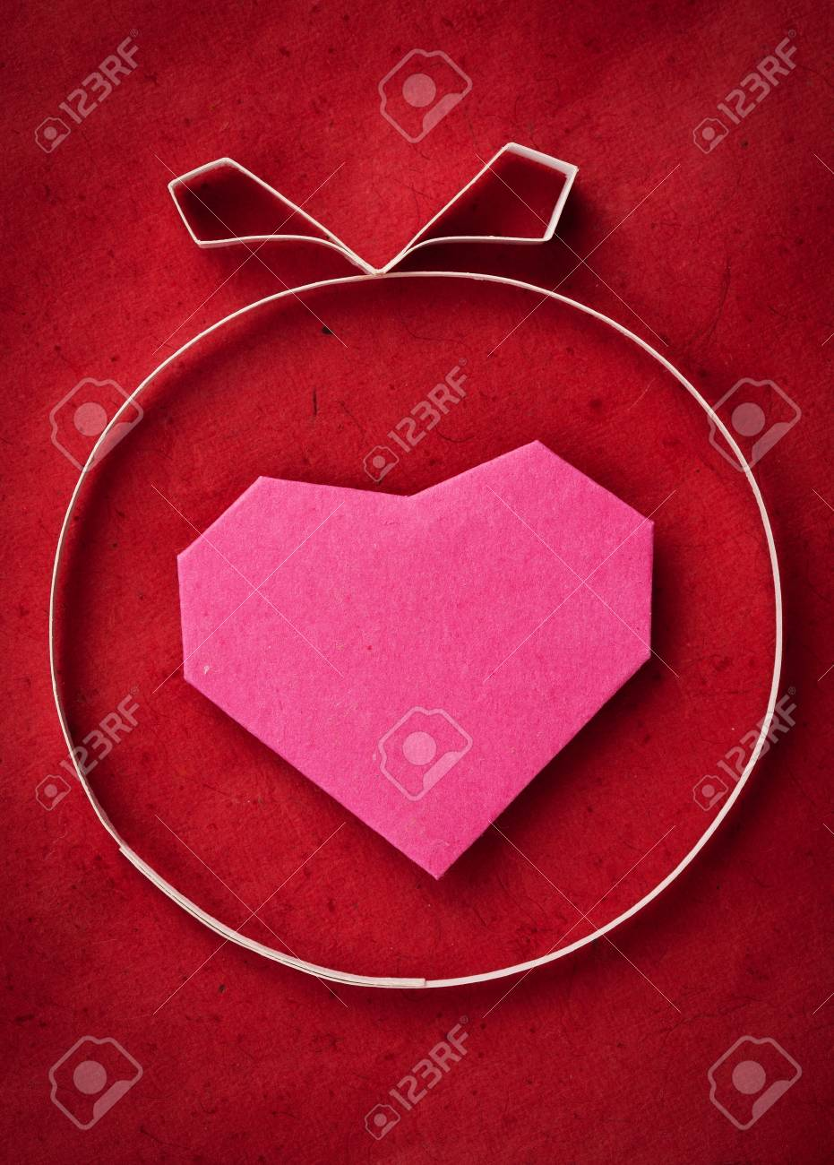 hand made paper heart on red kraft paper as background greeting