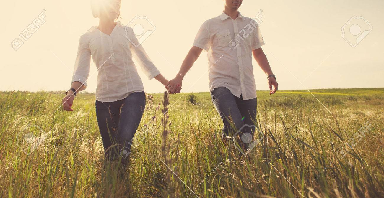 Happy couple holding hands walking through a meadow, tinted photo Stock Photo - 41752331