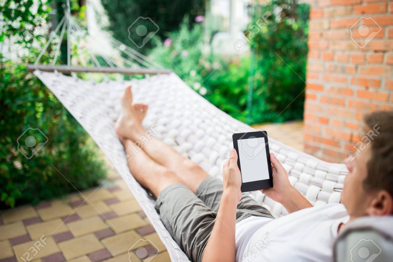 """Expresa tu momento """" in situ """" con una imagen - Página 2 62183680-hombre-que-usa-un-libro-electr%C3%B3nico-o-tablet-pc-mientras-se-relaja-en-una-hamaca-"""