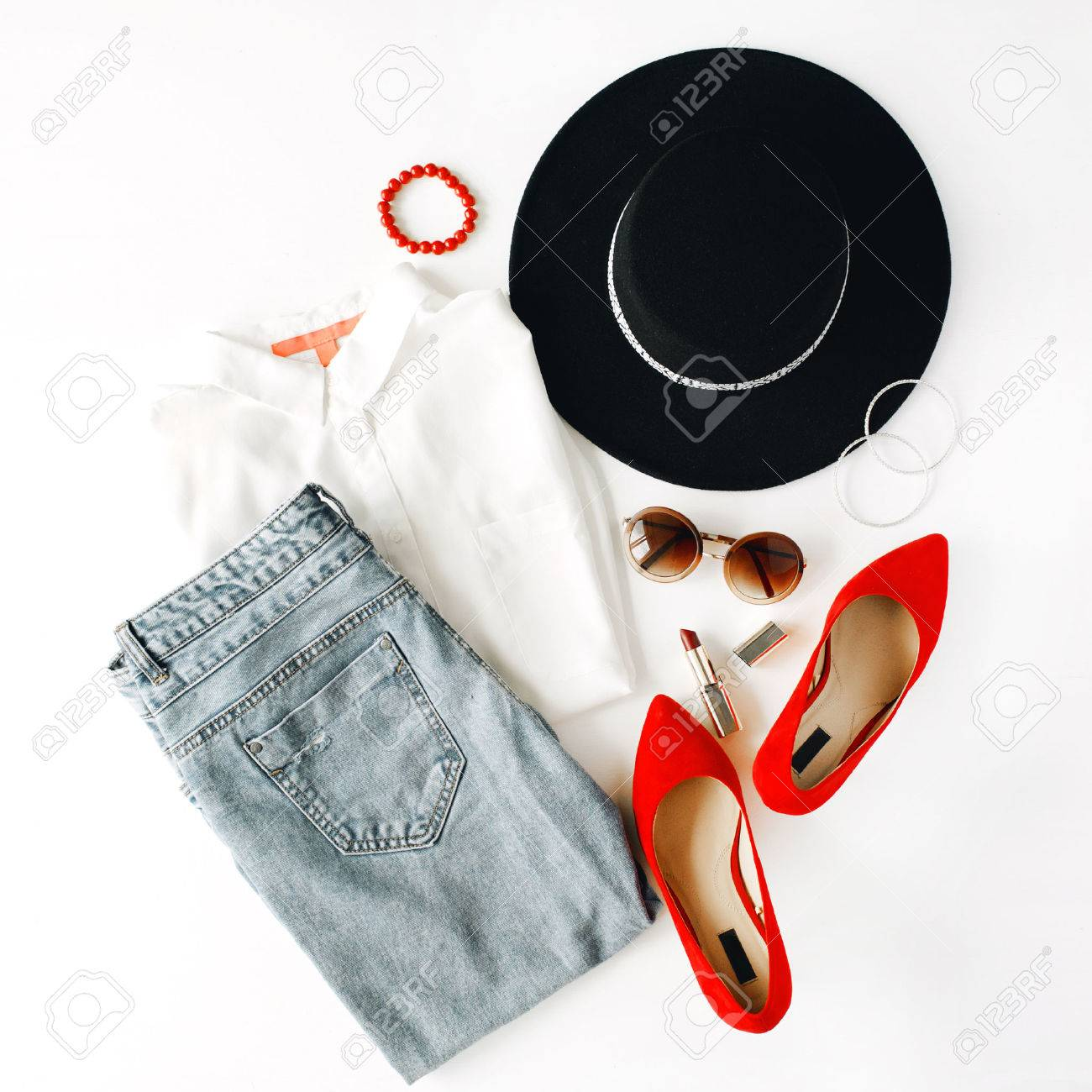 flat lay feminini clothes and accessories collage with blouse, jeans, sunglasses, bracelet, lipstick, red high heel shoes, earrings and hat on white background. - 60890716