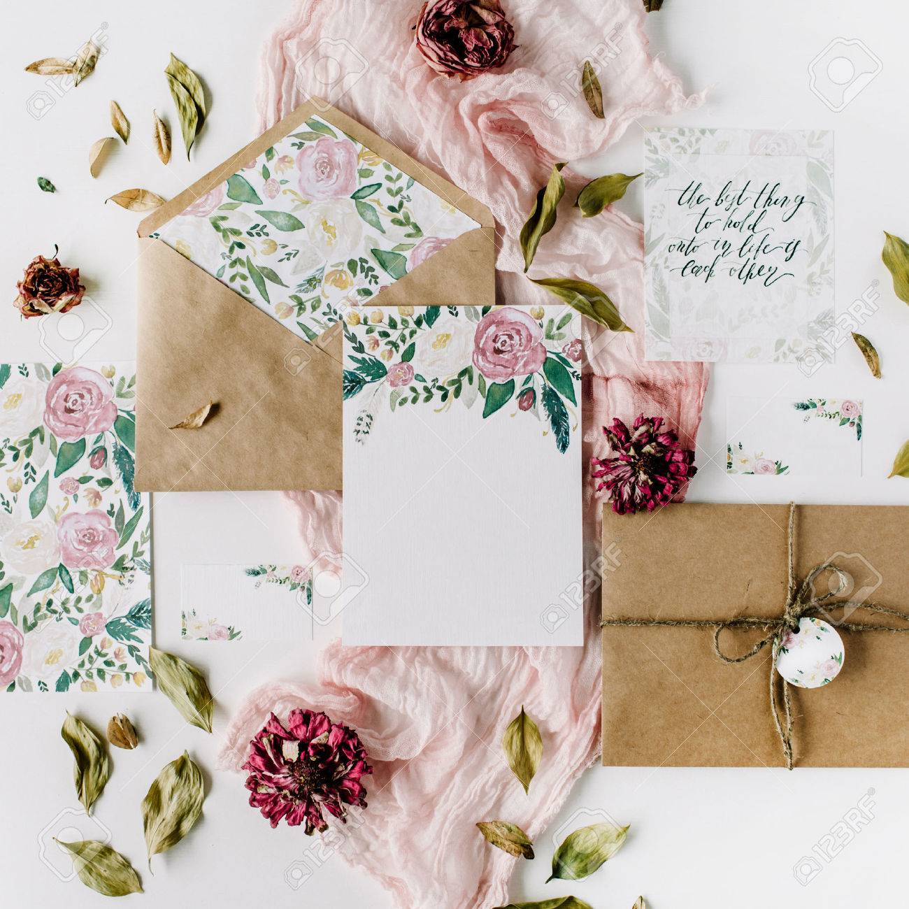 Workspace wedding invitation cards craft envelopes pink and wedding invitation cards craft envelopes pink and red roses and green leaves on white background overhead view flat lay top view stopboris Choice Image