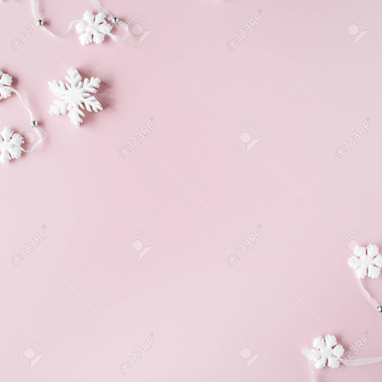 67718556 white christmas snowflakes decoration on pink background christmas wallpaper flat lay top view