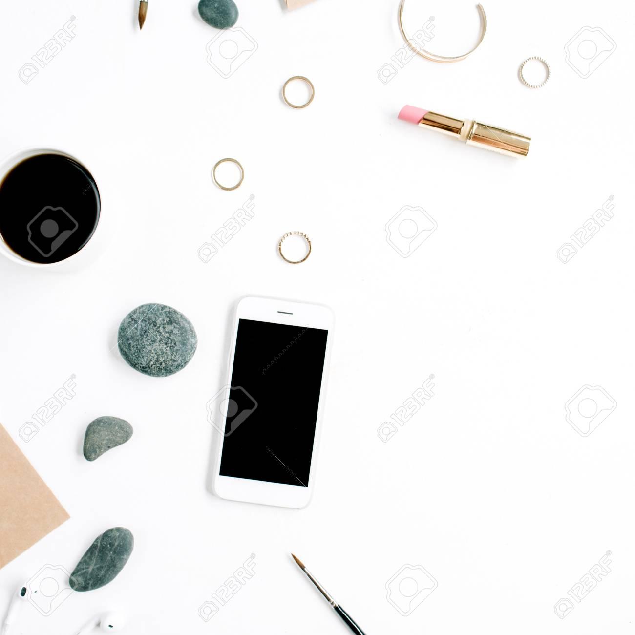 Espace de travail de bureau à domicile avec café, téléphone portable,  enveloppe de bricolage, pierres, écouteurs et papier vierge sur fond blanc  Lay