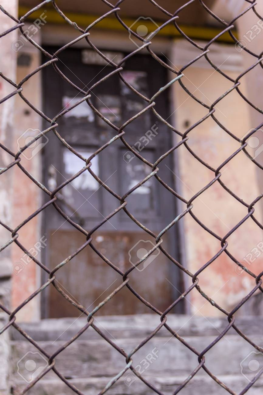 Rusty steel chain link or wire mesh as boundary wall. There is door behind the mesh. - 75044006