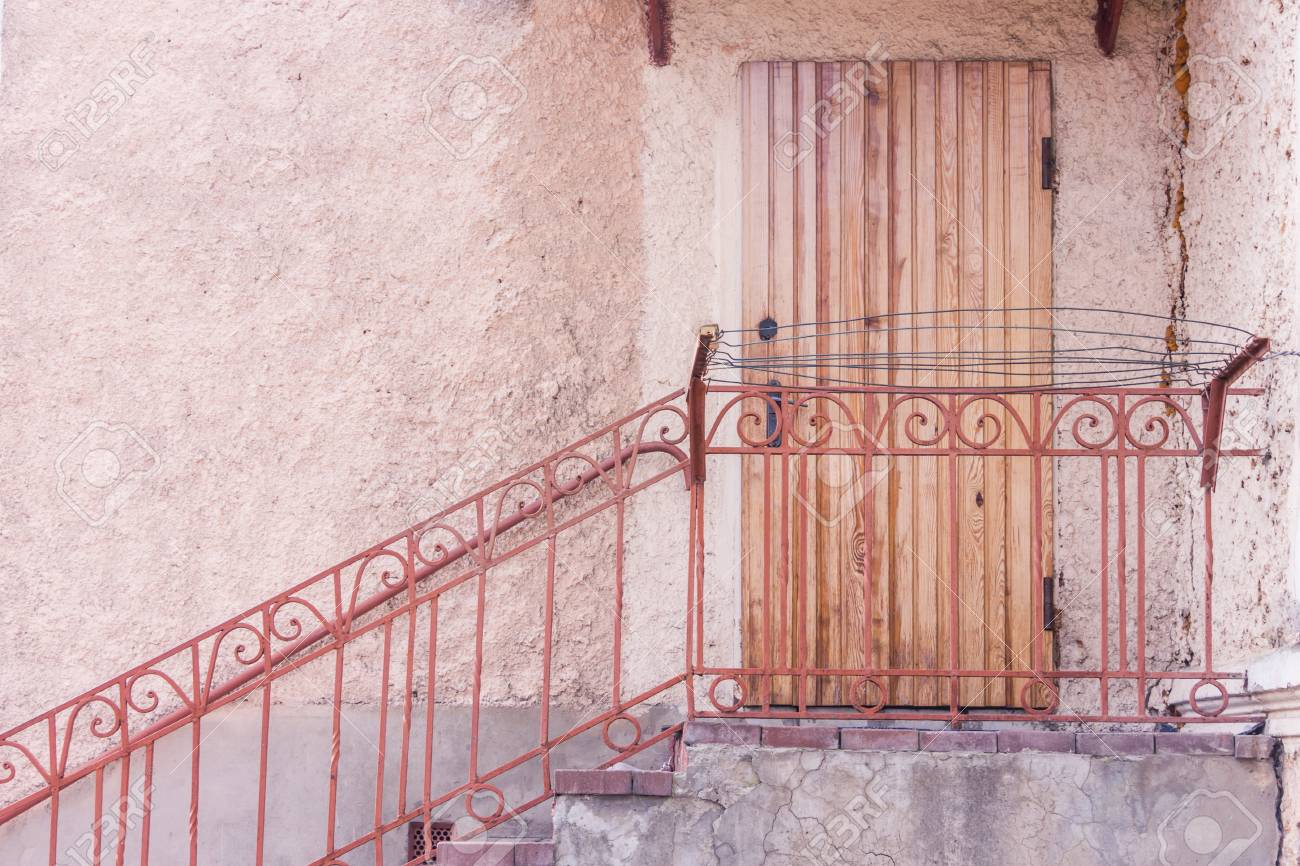 Entrance to the building through a brown wooden door. Steps with metal handrail - 74995045