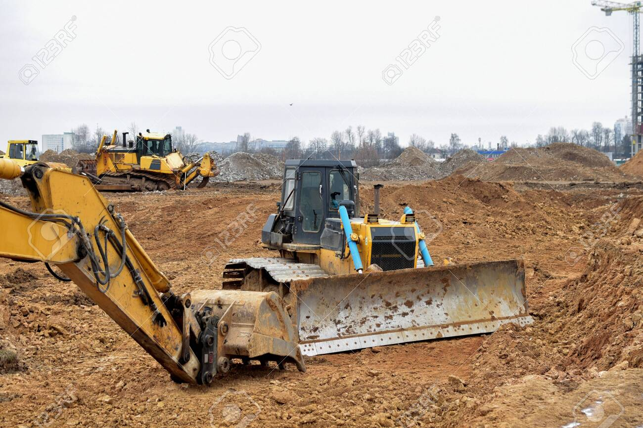 Excavator and a bulldozer work at a construction site. Land clearing, grading, pool excavation, utility trenching and foundation digging. Laying of underground storm sewer pipes. - 136426420