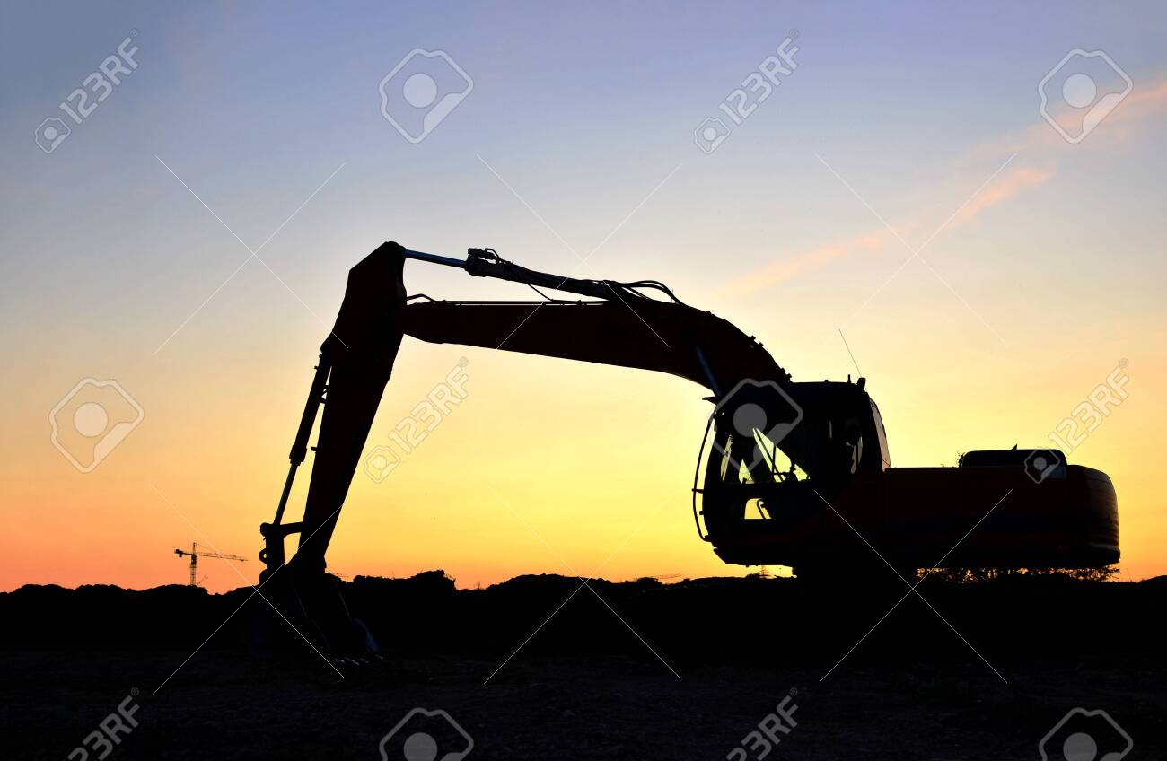 Silhouette of the heavy tracked excavator at a construction site on a background sunset. Special heavy construction equipment for road construction. Small roughness sharpness, possible granularity. - 137589845