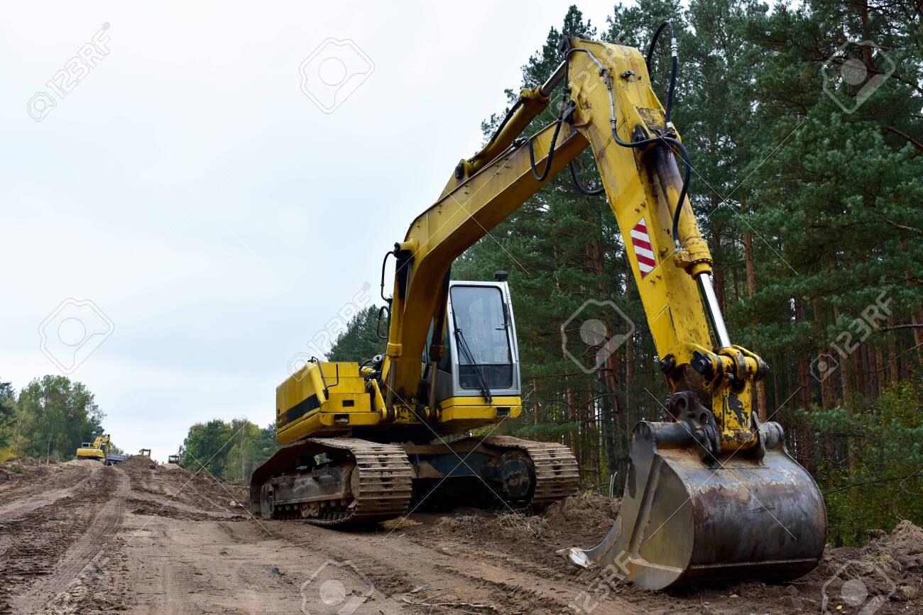 Excavator during construction new road in forest area. Yellow backhoe at groundwork. Earth-moving equipment fort road work, grading, pool excavation, utility trenching - 157562183