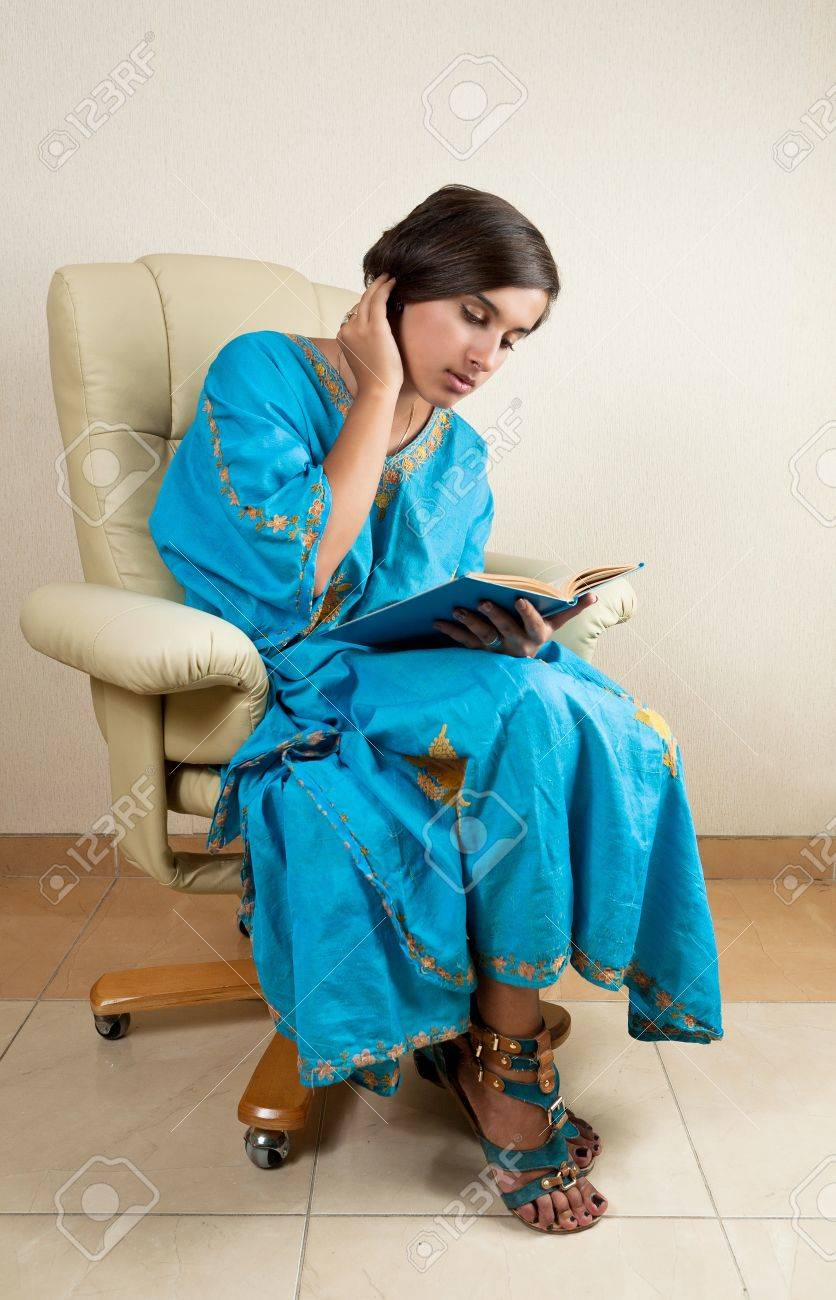 young girl sitting in chair reading book Stock Photo - 15259626