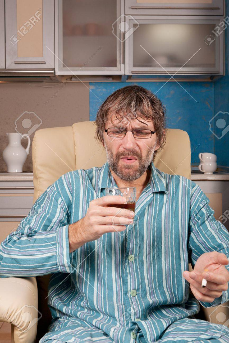 mature drunk man sitting in chair with glass and cigarette Stock Photo - 17277983