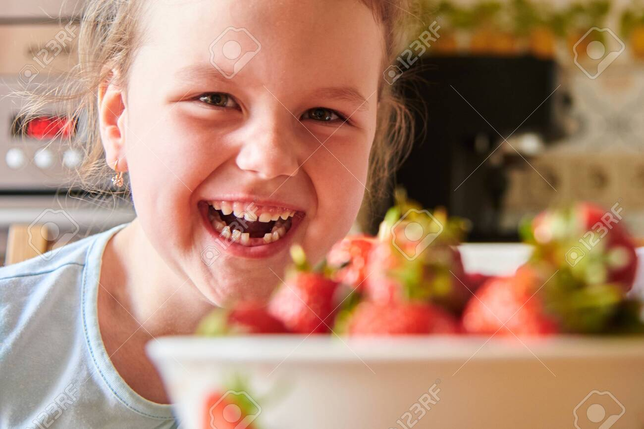 Beautiful European child in the kitchen eating strawberries and drinking milk. - 148704179