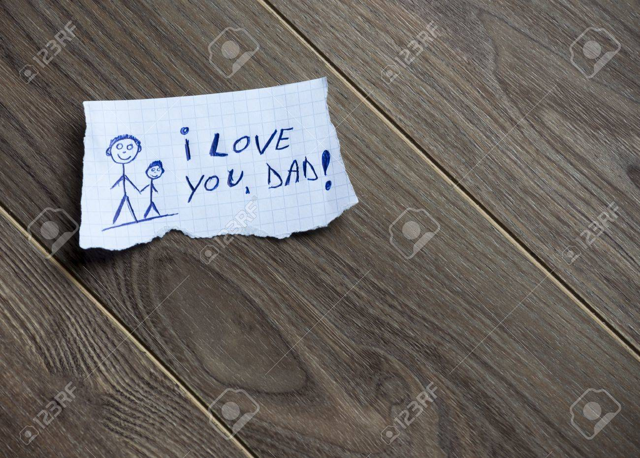 i love you dad written on piece of paper on a wood background i love you dad written on piece of paper on a wood background