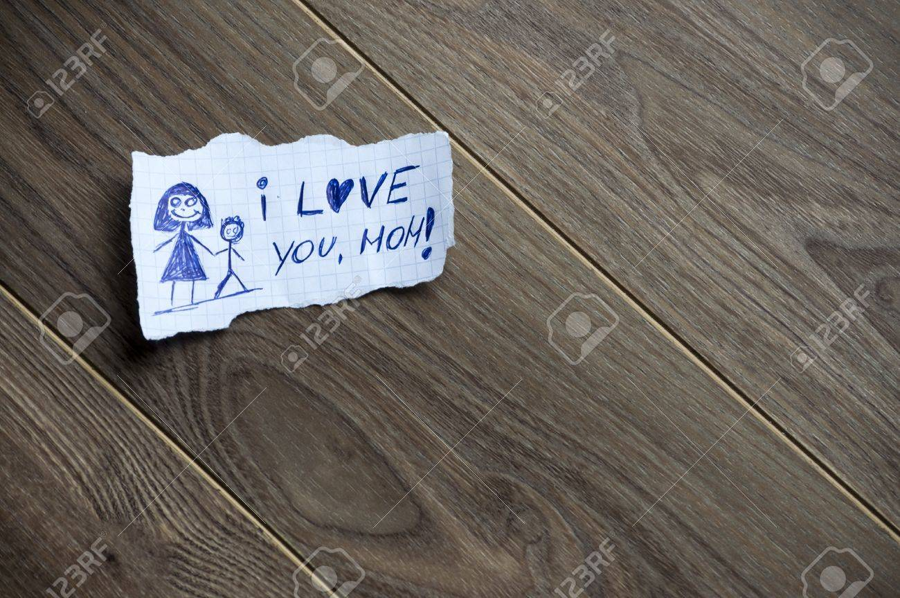 i love you mom written on piece of paper on a wood background i love you mom written on piece of paper on a wood background