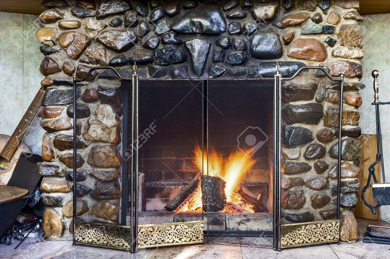 chimenea de piedra en la casa de campo y el fuego ardiendo en el interior con
