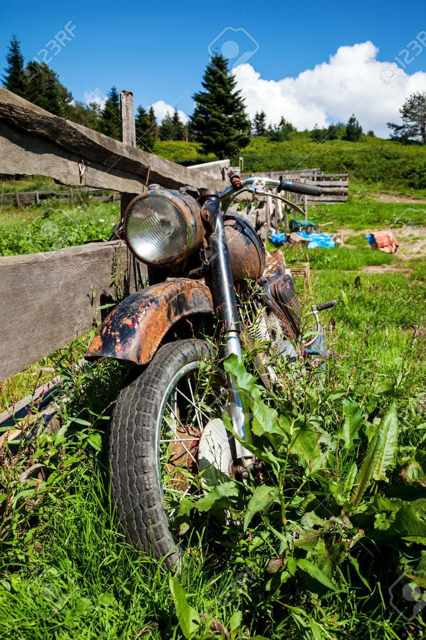 村の地方で古いバイクを断念しました。フェンスの近くの草を草に覆われ ...