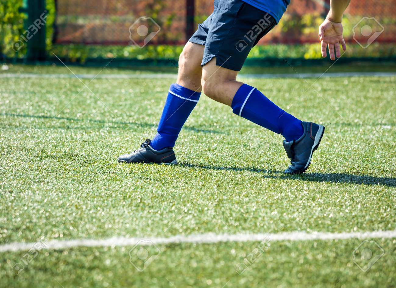 Legs of football player in motion on the field. Soccer player legs in  action Stock 00b408e216a
