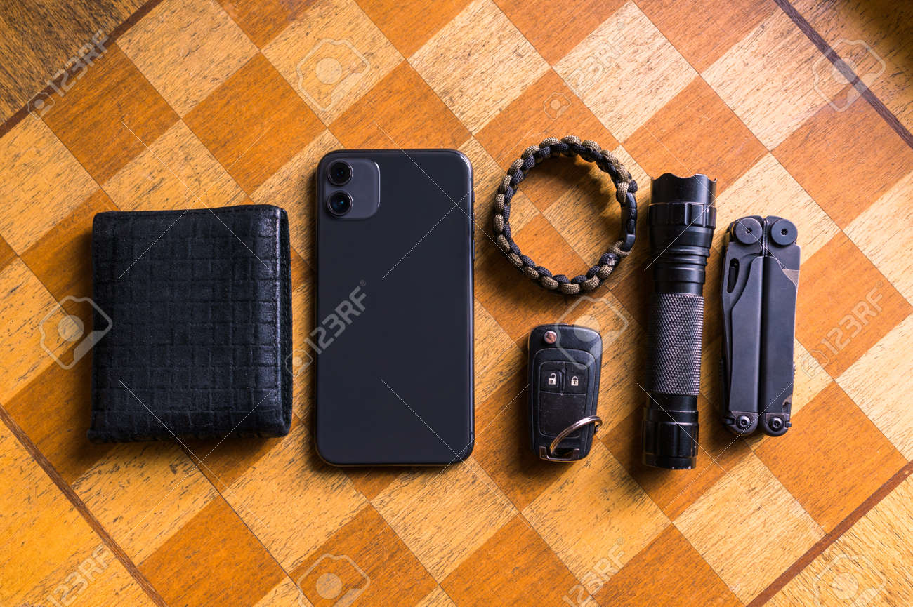 EDC setup. Concept on the wooden chess board. Everyday carry for a man. Knife, Multitool, Flashlight, Car key, Paracord bracelet, Wallet, Lighter, Smartphone... - 160603958