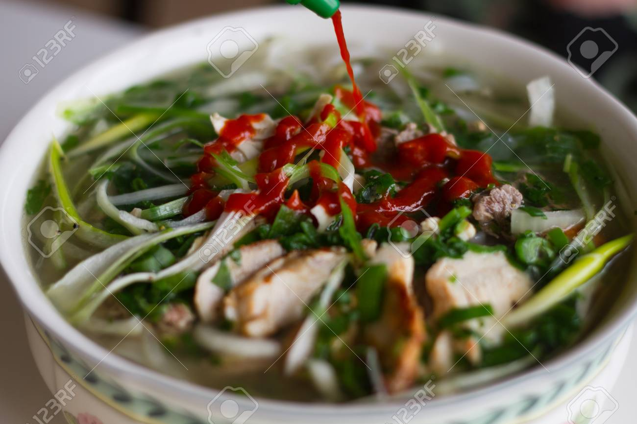 Vietnamese beef noodle soup Pho Bo with garnish of leaves of