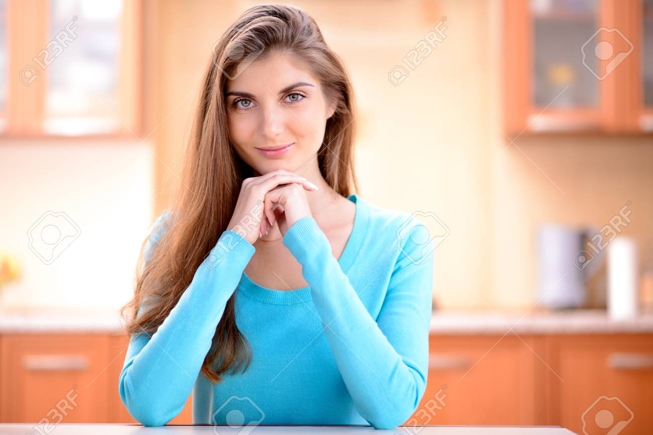 Portrait Of A Beautiful Young Lady Sitting In The Kitchen At.. Stock ...