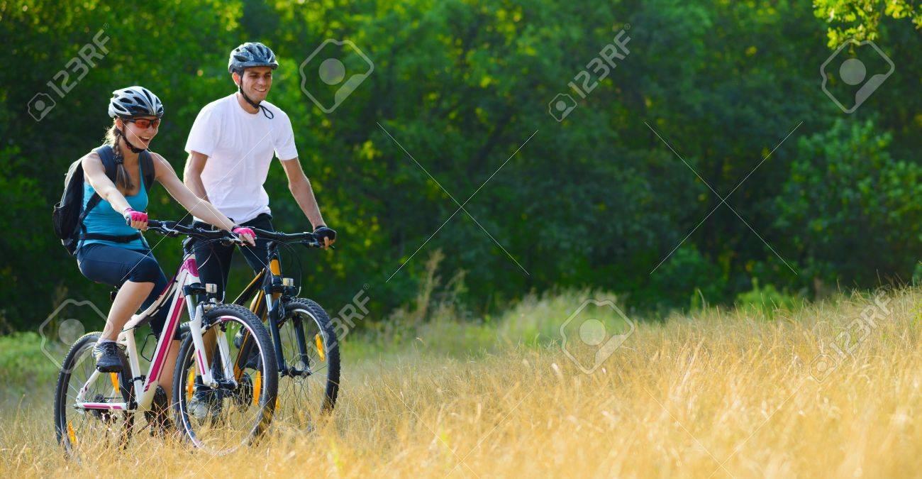 Young Happy Couple Riding Mountain Bikes Outdoor. Healthy Lifestile Concept - 21656230