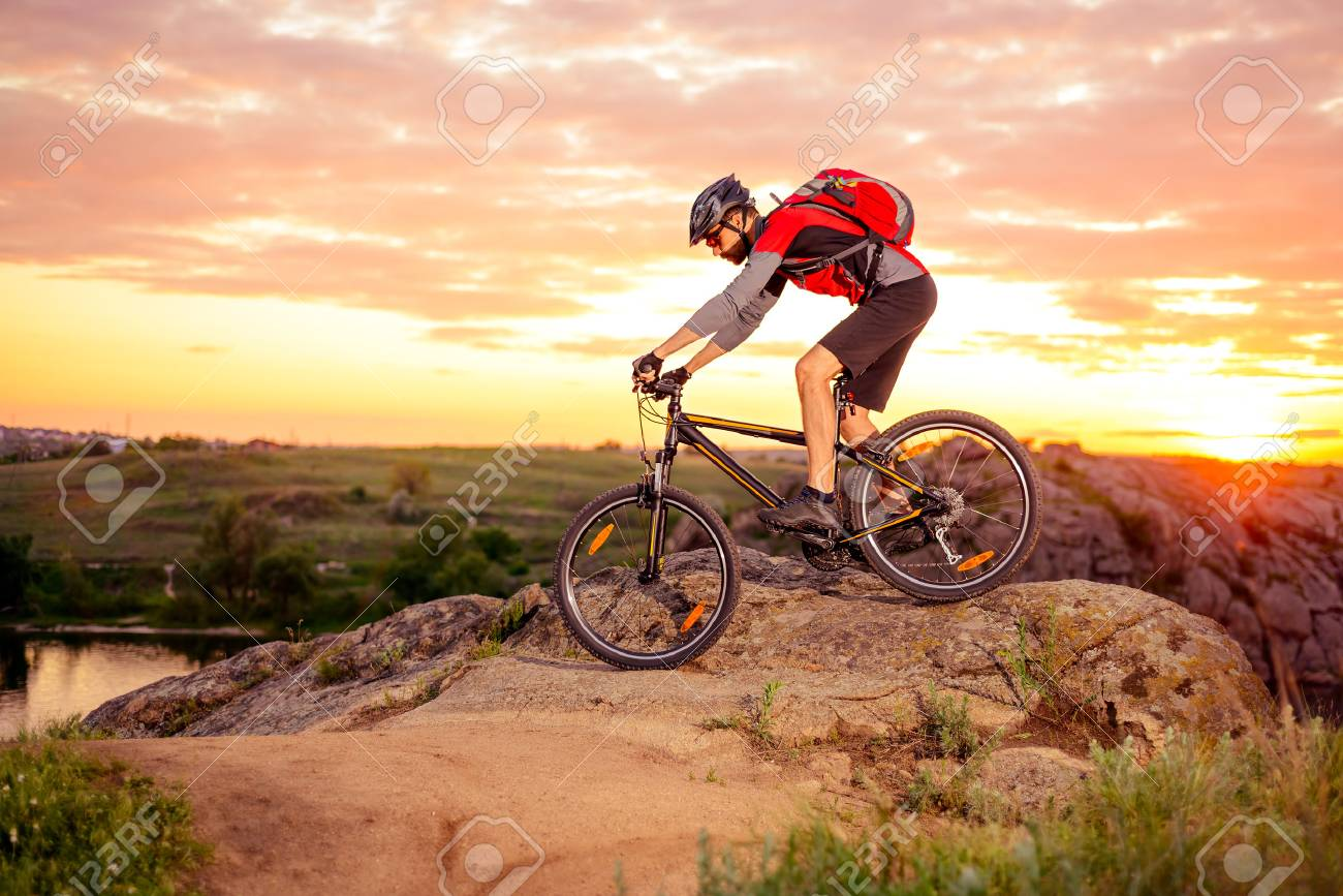 Cyclist Riding the Bike Down Hill on the Mountain Rocky Trail at Sunset. Extreme Sports - 61049121