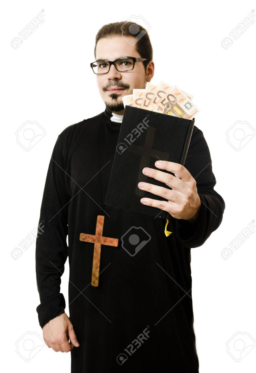 Priest holding bible with euro currency in pages symbol of religion priest holding bible with euro currency in pages symbol of religion and money focus biocorpaavc Images