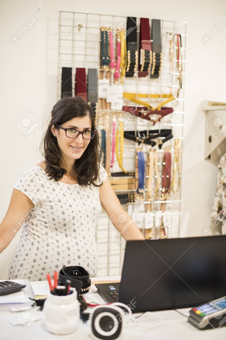 4694e9e25b2 Pregnant woman working in clothes store near to computer Stock Photo -  44839946