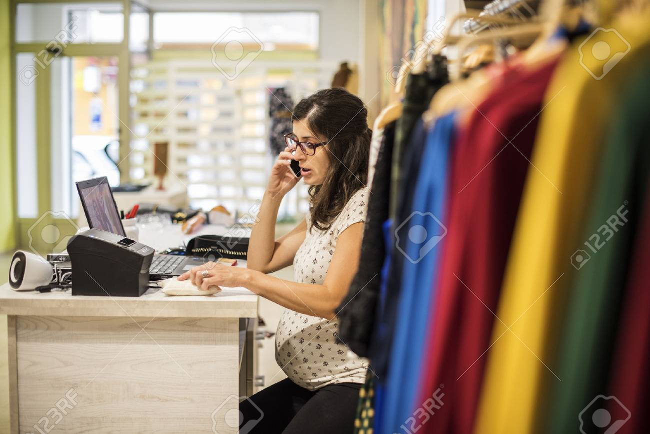 79eeb10e32c Pregnant woman working in clothes store near to computer Stock Photo -  44839967