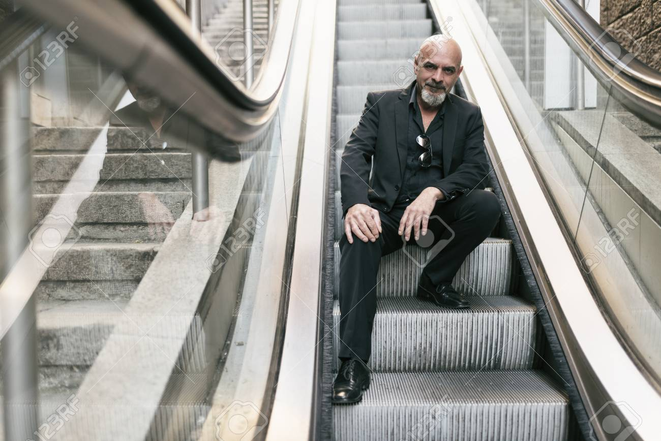Mature Man Looks At The Phone On Outdoor Escalator Stock Photo Picture And Royalty Free Image Image 121377733