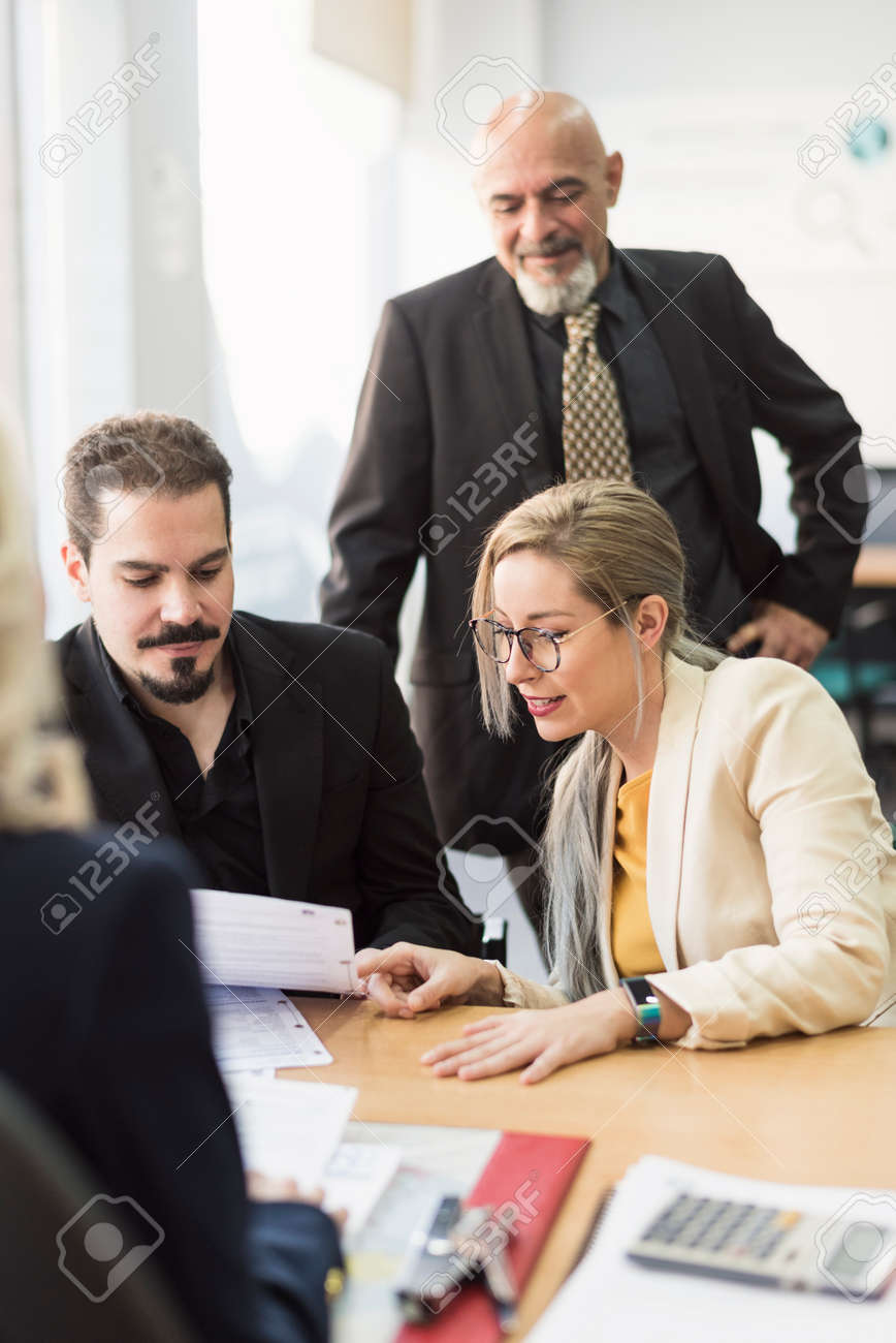 Group of workers in office looking papers in workplace - 121378583